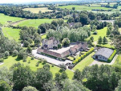 Attractive farmhouse; barns converted to 7 self-catering cottages; 15 acres; river frontage