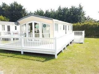 Willerby Windsor caravan on large pitch with wrap around decking and skirting